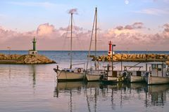 Cala Bona Port, fishing boats with reflections, cloudy sky and moon, Mallorca, Spain stock photography
