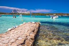 Cala Brandinchi strand met Isola Travolara in de achtergrond, de rode stenen en het azuurblauwe duidelijke water, Sardinige, Ital stock afbeeldingen