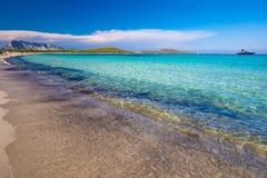 Cala Brandinchi strand met Isola Travolara in de achtergrond, de rode stenen en het azuurblauwe duidelijke water, Sardinige, Ital royalty-vrije stock foto's