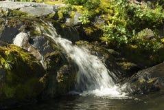 Cala de la montaña con una cascada Foto de archivo