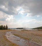 Cala enredada que corre en el lago caliente bajo cloudscape del cúmulo en el lavabo más bajo del géiser en el parque nacional de  Imagenes de archivo