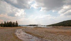 Cala enredada que corre en el lago caliente bajo cloudscape del cúmulo en el lavabo más bajo del géiser en el parque nacional de  fotos de archivo libres de regalías
