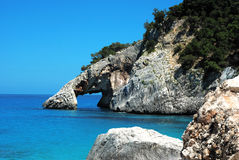 Cala goloritzè of Sardinia. Characteristic feature of the beach is the natural arch that opens on the right side of the bay Stock Images