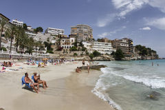 Cala major beach in mallorca. People sunbath during summer at beach in the island of Mallorca, Spain Stock Photos