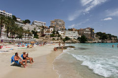 Cala major beach in the spanish oj mallorca. People sunbath during summer at beach in the spanish balearic island resort of Mallorca, Spain Stock Photo