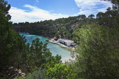 Cala Pi beach. CALA PI, MALLORCA, SPAIN - APRIL 29, 2017: Cala Pi beach with natural shrub vegetation, steep cliffs, tourists and buildings on April 29, 2017 in Royalty Free Stock Images