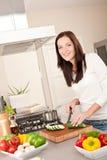 Calabacín feliz del corte de la mujer en la cocina foto de archivo