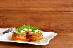 Calabacín frito con los tomates frescos, el yogur y el perejil verde foto de archivo