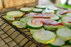 Calabacín verde dietético con las rebanadas de tocino jugoso que fríen en una parrilla sobre un fuego S Imágenes de archivo libres de regalías