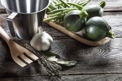 Calabacines redondos y habas verdes con los utensilios de la cocina Imágenes de archivo libres de regalías
