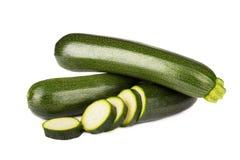 Calabacín y rebanadas de las verduras frescas en el fondo blanco Foto de archivo