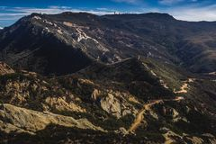 Calabasas Peak Trail. Picturesque overlook of Calabasas Peak Trail winding through the canyon with rock formations on a sunny day with blue sky and clouds Stock Photo
