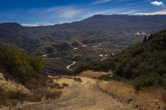 Calabasas Peak Trail. Picturesque overlook of Calabasas Peak Trail winding through the canyon with rock formations on a sunny day with blue sky and clouds Royalty Free Stock Images