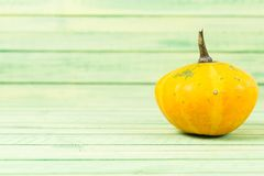 Calabaza amarilla del otoño en fondo de madera verde Foto de archivo