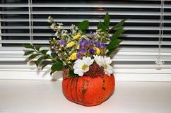 Calabaza con las flores en el alféizar en Halloween Foto de archivo libre de regalías
