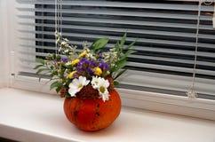 Calabaza con las flores en el alféizar en Halloween Foto de archivo