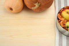 Calabaza con las manzanas y las frutas secadas en fondo de madera Imágenes de archivo libres de regalías