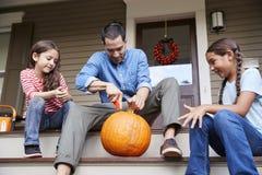 Calabaza de And Daughters Carving Halloween del padre en pasos de la casa foto de archivo