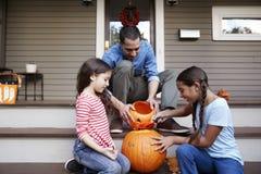 Calabaza de And Daughters Carving Halloween del padre en pasos de la casa foto de archivo libre de regalías