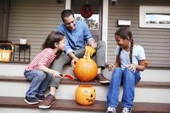 Calabaza de And Daughters Carving Halloween del padre en pasos de la casa fotografía de archivo libre de regalías