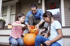 Calabaza de And Daughters Carving Halloween del padre en pasos de la casa imagenes de archivo