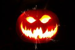 Calabaza de Halloween con la cara y las chispas asustadizas Imágenes de archivo libres de regalías