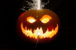 Calabaza de Halloween con la cara y las chispas asustadizas Fotografía de archivo libre de regalías