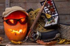 Calabaza de Halloween con vadear botas y la pesca con mosca Imágenes de archivo libres de regalías