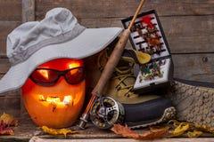 Calabaza de Halloween con vadear botas y la pesca con mosca Foto de archivo libre de regalías