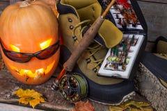 Calabaza de Halloween con vadear botas y la pesca con mosca Imagenes de archivo