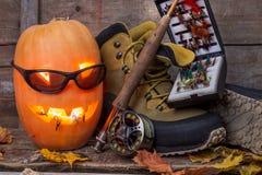 Calabaza de Halloween con vadear botas y la pesca con mosca Fotos de archivo