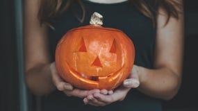 Calabaza de Halloween en las manos de una muchacha con las luces de Bengala Concepto de Halloween del día de fiesta Mujer hermosa imagen de archivo