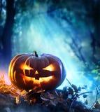 Calabaza de Halloween en un bosque fantasmagórico en la noche Fotografía de archivo libre de regalías