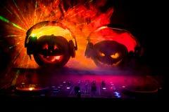 Calabaza de Halloween en una tabla de DJ con los auriculares en fondo oscuro con el espacio de la copia Decoraciones y música del imágenes de archivo libres de regalías