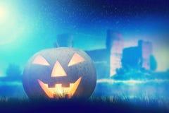 Calabaza de Halloween que brilla intensamente en paisaje oscuro, brumoso Imagen de archivo