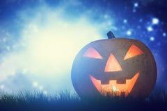 Calabaza de Halloween que brilla intensamente en paisaje oscuro, brumoso Foto de archivo