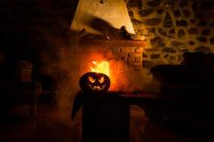 Calabaza espeluznante de Halloween cerca de una chimenea Fuego en el fondo fotos de archivo