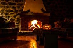 Calabaza espeluznante de Halloween cerca de una chimenea Fuego en el fondo foto de archivo libre de regalías