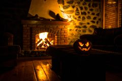 Calabaza espeluznante de Halloween cerca de una chimenea Fuego en el fondo fotografía de archivo libre de regalías