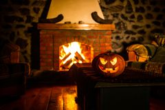 Calabaza espeluznante de Halloween cerca de una chimenea Fuego en el fondo imagen de archivo libre de regalías