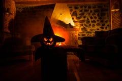Calabaza espeluznante de Halloween cerca de una chimenea Fuego en el fondo imagenes de archivo