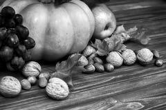 Calabaza, manzana, nueces, hojas en fondo de madera Foto de archivo libre de regalías