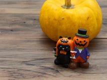 Calabaza orgánica amarilla e individuo de cerámica miniatura anaranjado de la calabaza con el gato negro en fondo de madera oscur Imagen de archivo libre de regalías