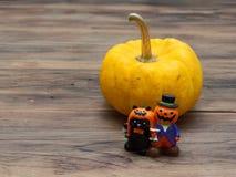 Calabaza orgánica amarilla e individuo de cerámica miniatura anaranjado de la calabaza con el gato negro en fondo de madera oscur Imagenes de archivo