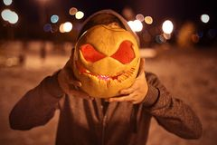 Calabaza para Halloween en cara asustadiza de las manos Fotos de archivo