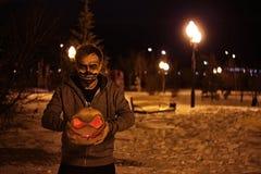 Calabaza para Halloween en cara asustadiza de las manos imagen de archivo