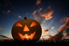 Calabaza que brilla intensamente bajo puesta del sol oscura, cielo nocturno de Halloween Gato O'Lantern Imágenes de archivo libres de regalías