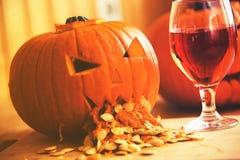 Calabaza que vomita con las semillas de calabaza en la tabla de madera, vidrio de vino, efecto del vintage Foto de archivo