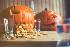 Calabaza que vomita con las semillas de calabaza en la tabla de madera, vodka, efecto del vintage Foto de archivo