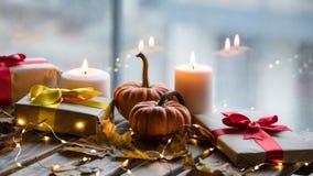 Calabaza, regalos y velas con las hojas de arce Fotos de archivo